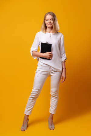 Business coaching. Self development growth. Professional career. Corporate life. Portrait of smart confident woman in white with clipboard looking at camera isolated on orange background.