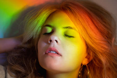 Rainbow portrait. Inner peace. Soul recreation. Freedom harmony. Relaxed blonde woman sleeping in bright color gradient glowing neon light. Stock Photo