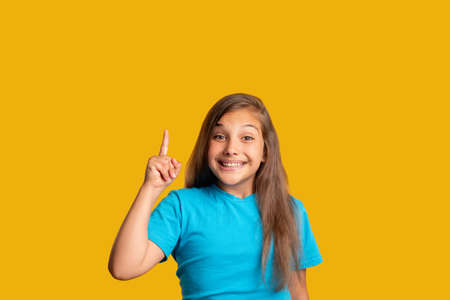 Surprised young girl in blue t-shirt pointing up at copy space isolated on orange commercial background.