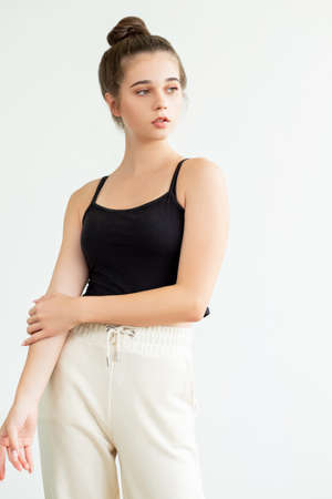 Sportive clothes. Casual fitness outfit. Pretty young woman in black sleeveless top white trousers and bun hairstyle posing like model isolated on neutral. Trend look advertising