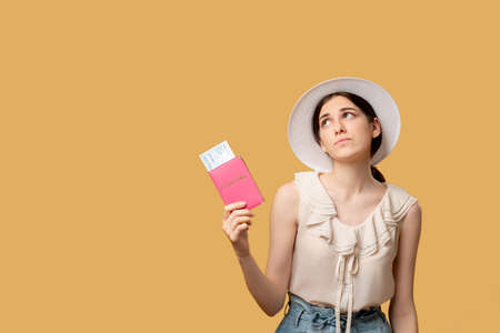 Holiday trip. Delayed flight. Summer tour. Information banner. Thoughtful disappointed woman looking up holding foreign passport tickets isolated on beige copy space.