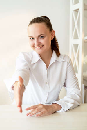 Corporate meeting. Career promotion. Partnership cooperation. Success congratulations. Confident cheerful woman with welcoming new employee with handshake at light modern workspace.