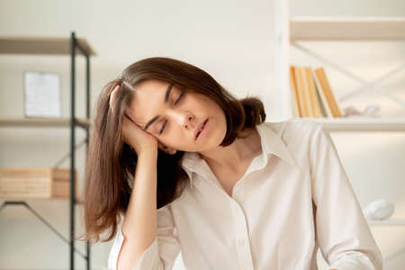 Young tired woman in white shirt sleeping leaning head on hand workplace interior background.