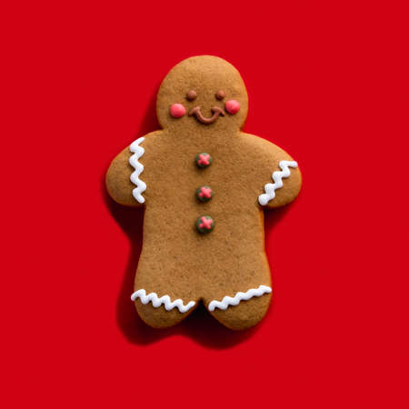 Christmas cookie. Festive pastry. Homemade biscuit. Brown happy gingerbread man decorated with white icing smiling isolated on red background.