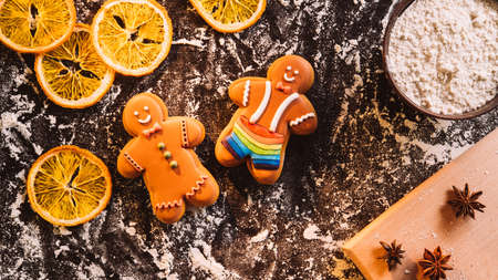Christmas bakery. Gingerbread man. cookies. Traditional pastry. Homemade biscuits. Figured icing bakery house holiday tree present on flour powdered dried orange spices black desk.