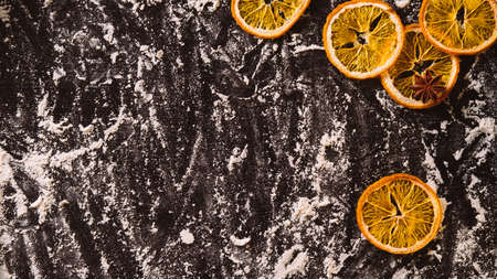 Christmas food background. Festive decoration. Homemade culinary. Meal powdered black desk with dried orange and star anise spices copy space. Advertising background. Reklamní fotografie