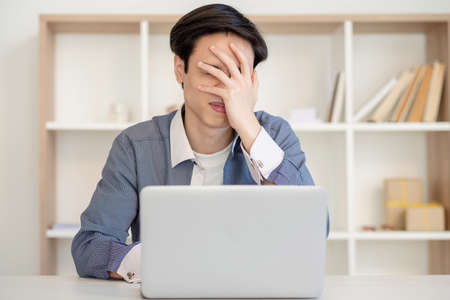 Desperate employee. Task failure. Remote job. Startup crash. Frustrated stressed asian man working with laptop showing facepalm gesture at light home office.