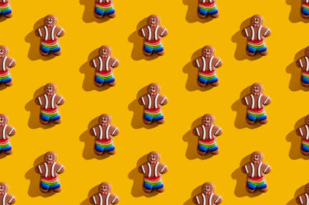 Lgbt pride. Orange seamless background. Diversity tolerance. Bakery food art conceptual ornament. African gay gingerbread man in rainbow shorts minimalist composition isolated on bright yellow. Imagens
