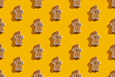 Orange seamless background. Gingerbread man pattern. Brown cookie cute ornament poster design for children. Creative minimalist composition isolated on bright yellow.