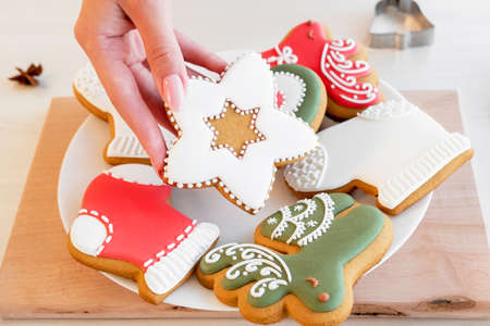 Gingerbread cookies. Traditional festive culinary. Unrecognizable female hand holding icing pastry biscuit star figure from white plate.