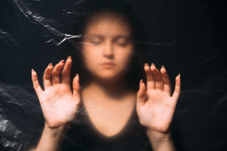 Peaceful woman. Defocused art portrait. Soul healing. Wrinkled texture female silhouette with closed eyes touching plastic polyethylene film with hands isolated on black out of focus.