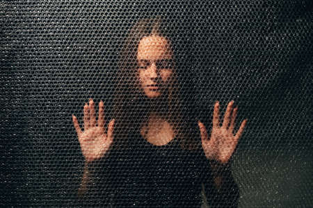 Peaceful woman. Soul healing. Spiritual practice. Esoteric mystery. Textured portrait of relaxed lady in black touching plastic wall in darkness.