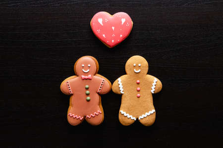 Gay love. Valentine Day. Black conceptual background. Romantic relationship. Happy gingerbread man cookie couple with red heart in love creative arrangement on black wooden texture empty space. Imagens