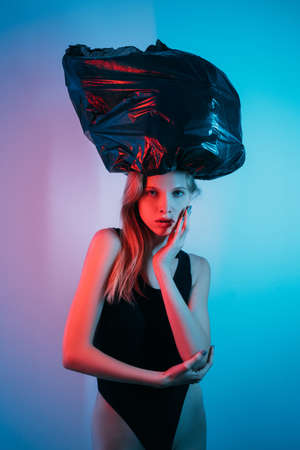 Art portrait. Heavy burden. Stress weight. Anxiety problem. Exhausted pensive woman suffering from pressure of black bag on head in red neon light isolated on blue pink color gradient background. Standard-Bild