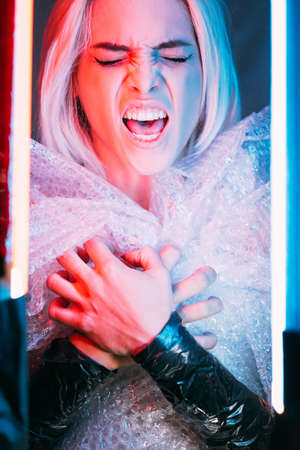 Screaming female portrait. Plastic pollution. Garbage danger. Save planet. Crying out woman grabbing hands on chest in bubbles polyethylene film dress on blue pink neon light background. Imagens