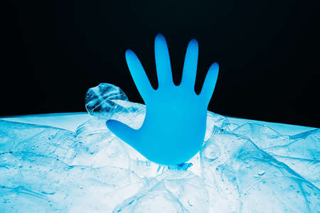 Stop pollution. Save Earth. Waste reduction. Ecology problem. Blown blue medical hand glove floating in space over abstract planet contaminated with plastic bottles isolated on black background.