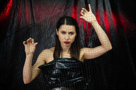 Fashion art. Gothic beauty. Female freedom. Feminist empowerment. Mysterious brunette woman in black trapped in mesh cage in dark night abstract cave background with red glow.