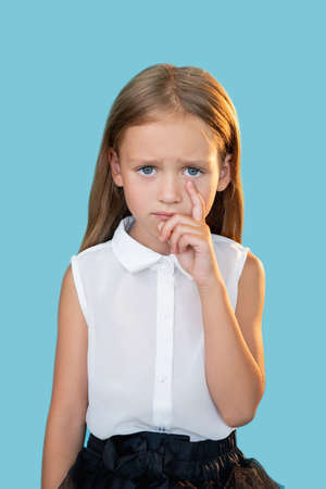 Offended kid. Unfair punishment. Sorrow disappointment. Portrait of unhappy crying sweet little girl in elegant outfit wiping tear with finger isolated on blue background.