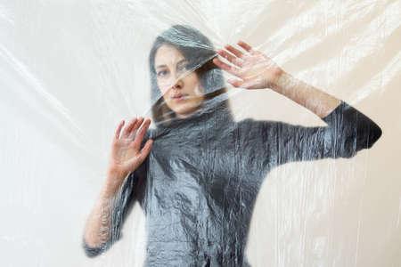 Defocused art portrait. Psychology crisis. Social distance. Barrier isolation. Helpless sad woman touching transparent plastic film isolated on neutral blur.