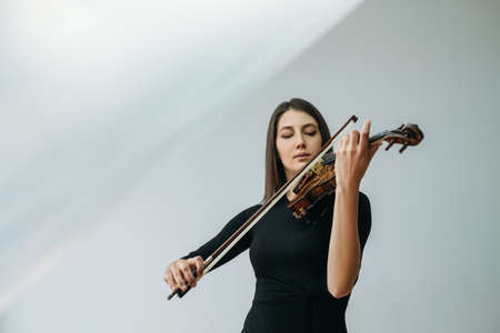 Violinist woman. Online education. Distance lesson. Lockdown reality. Inspired lady enjoying playing violin closed eyes with transparent plastic film under head isolated neutral copy space. Standard-Bild