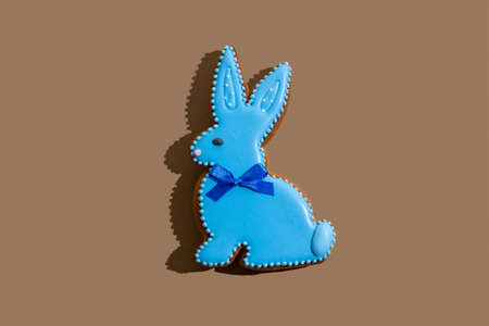 Happy easter. Gingerbread bunny. Festive bakery. Spring holiday celebration. Sweet animal figure cookie with blue icing decoration isolated on beige copy space.