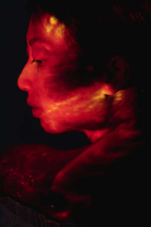 Art portrait. Passion energy. Spiritual aura. Esoteric recreation. Profile silhouette of sensual red Asian woman face with abstract orange light flecks on skin isolated on black background.