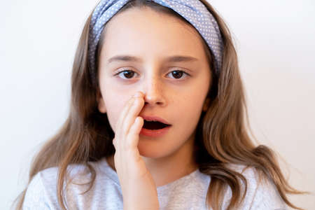 Child secret wish. Kid privacy. Confidential information. Portrait of cute brunette small girl whispering sharing gossip hiding open mouth with hand isolated on light neutral background. Stock Photo