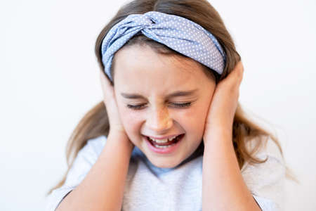 Disobedient kid. Child discipline. Temper tantrum. Portrait of naughty disturbed anxious small girl screaming covering ears with closed eyes isolated on white background.
