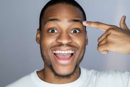 Enthusiastic African man. Aha moment. Self motivation. Portrait of happy astonished handsome dark skin guy in white pointing at face temple smiling isolated on gray background. Stock Photo