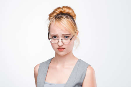 unsolved: Young nice woman in glasses worried, upset and perplexed of problem. Unsolved situation, inability to concentrate, failure. Portrait on grey background.