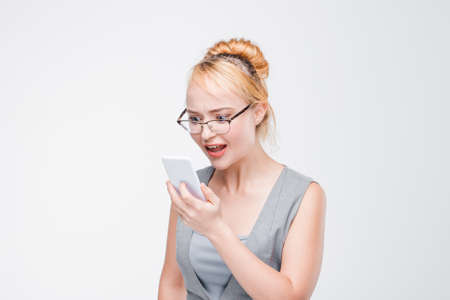 Irritated young girl in glasses with mobile phone looks angry, peeved and irritated. Annoyed and grumpy blonde with smartphone on grey background with copy space.