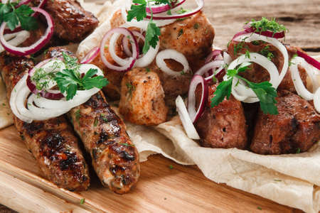 Appetizing assortment of grilled meat on pita bread decorated with onion and herbs, close up view. Restaurant menu photo. Stock Photo