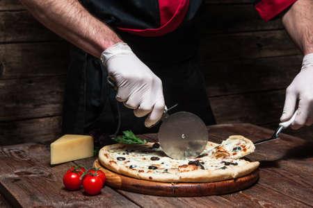 Cours de maître culinaire. Cuisine italienne. Chef coupe tranche de savoureuse pizza fraîche sur une table en bois rustique.