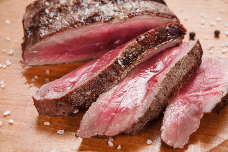 Thick slices of superior grilled meat served on wooden table, close up view. Restaurant menu photo. Gourmet concept Stock Photo