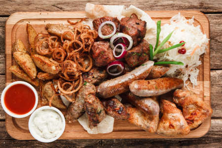Mixed grilled meat and sausages on wooden board. Assorted delicious meal served on pita bread with fried potato wedges, onion rings, sauerkraut and sauces, flat lay. Stock Photo