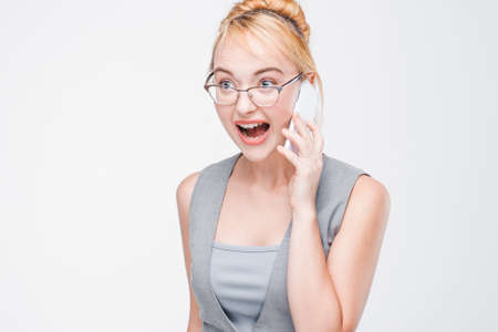 Aggressive irritated woman screaming and yelling talking on mobile phone. Inability to calm down, personal troubles, nervousness. Grey background with copy space. Stock Photo