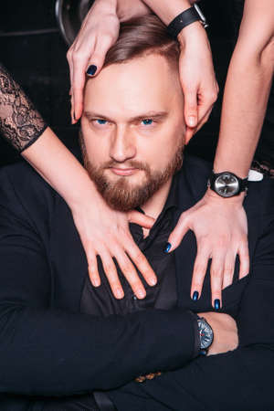 passionately: Portrait of young blue eyed handsome bearded macho man wanted by women passionately. Unrecognizable womens hands touching his head and shoulders with desire. Stock Photo