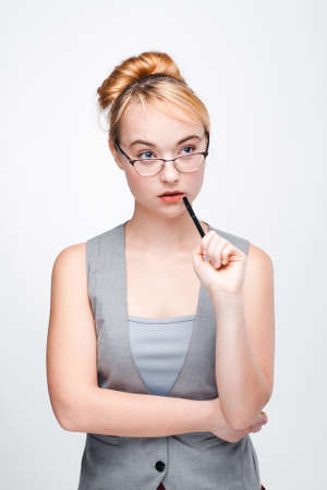 Young nice woman in glasses thinks of solving problem with pen near mouth, concentrated on finding right decision. Fair-haired thoughtful woman brainstorming on grey background.