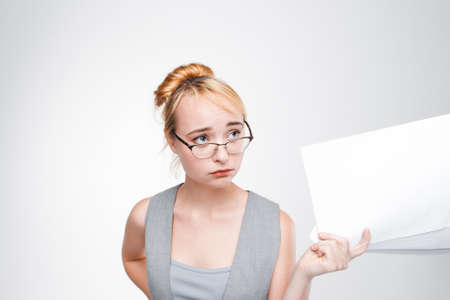 Young woman in glasses with papers in hand feels disappointed, grieved, sad and chagrined. Failure, bad luck, life or business problems. Grey background with copy space. Stock Photo
