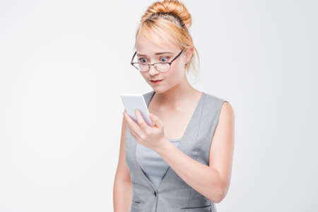 Young woman in glasses with mobile phone looks angry, peeved and irritated. Annoyed and grumpy blonde with smartphone on grey background with copy space.