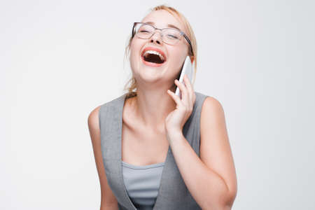 laughing out loud: Young blonde in glasses and vest laughing out loud talking on cell phone. Good joke, happy mood, positive emotions. Grey background with copy space.