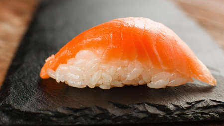 Appetizing and fresh one nigiri salmon sushi served on black slate, close up. Japanese seafood, healthy food. Stock Photo