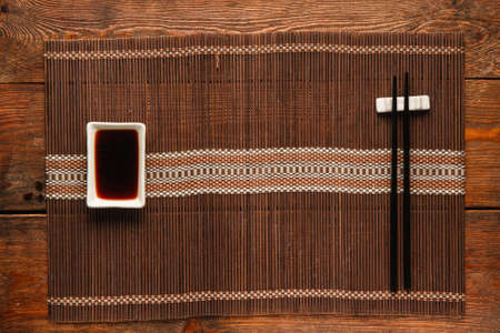 Japanese food background. Served table with empty straw mat for traditional oriental meal. Chopsticks and soy sauce served on wooden dark rustic surface, flat lay, void