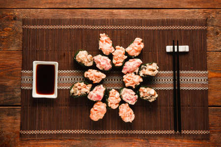 asian art: Set of appetizing fresh gunkan sushi rolls served on brown straw mat, flat lay. Japanese national seafood, restaurant menu photo, food art. Stock Photo