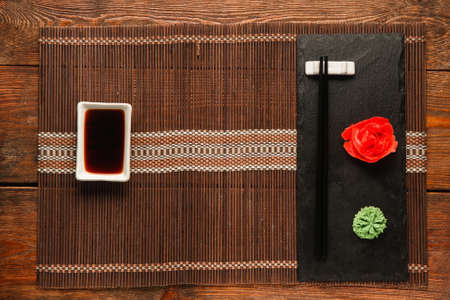 Japanese food background, table served for sushi, flat lay. Empty straw mat with soy sauce and black slate with chopsticks, wasabi and ginger.