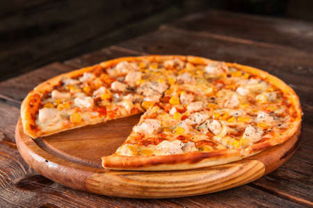 Junk food, bad habits. Pizza sliced on rustic wooden table background. Italian traditional meal