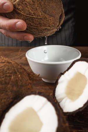 Fresh coconut milk pouring into white bowl on wooden table Preparing skin scrub, making massage oil, natural cosmetics concept