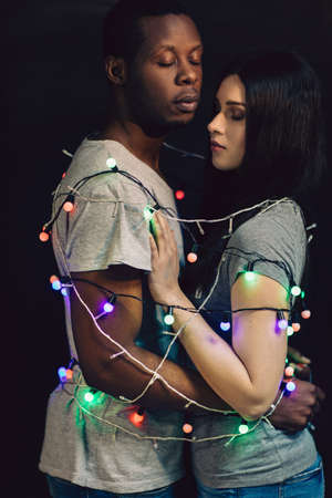 Couple in love tied together with sparkling garland. Black man and white woman, togetherness, unity and connection. Interracial happy relationship.