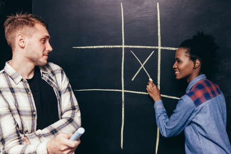 sexes: Interracial happy couple, white man and black woman play tic tac toe game. Fun leisure, great entertainment, joy and happiness, battle of the sexes concept. Stock Photo