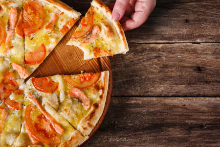 Junk food, bad habits, unhealthy eating. Unrecognizable person takes bitten slice of pizza served on dark wooden table background.
